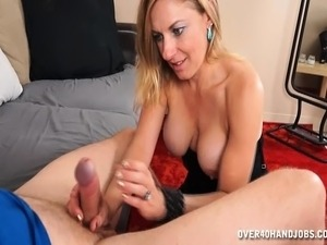 Horny blonde cougar with big boobs strokes a thick cock in an erotic handjob