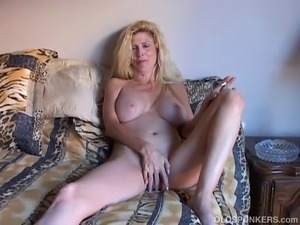 Awesome older blonde babe with an amazing rack lies back and frigs her...