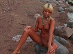 Elegant blonde gets naked on the beach in an erotic solo shoot