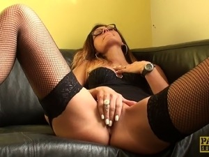 Horny bitch in glasses and fishnet stockings vibrating her shaved cunt