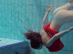 Red haired girl Libuse swimming in a pool in fire red dress
